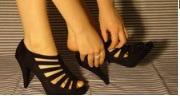 両足でパンプスを試し履きする画像